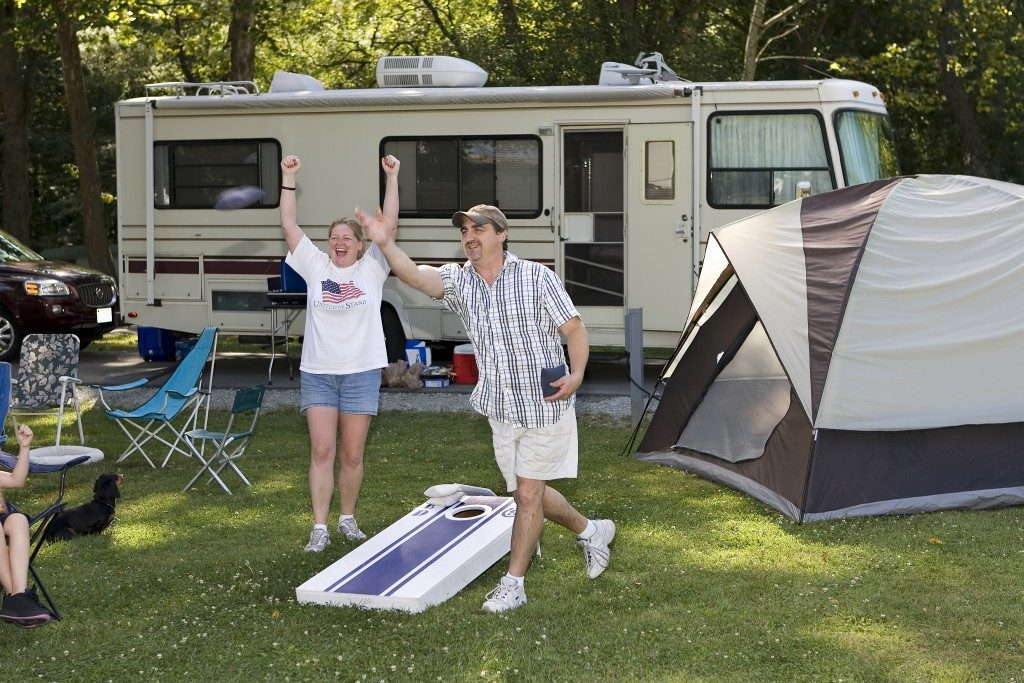 couple on a camping site playing cornhole