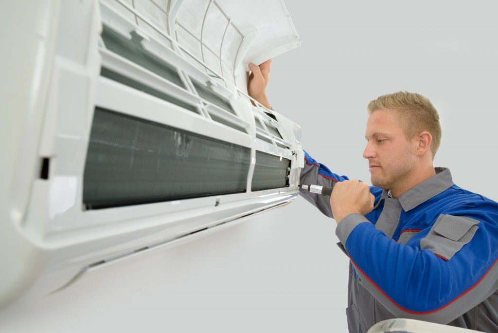 Portrait Of Young Male Technician Repairing Air Conditioner