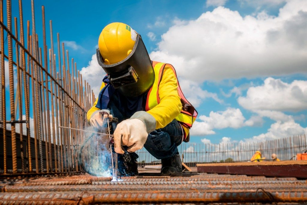 Construction worker wearing protective gear while welding