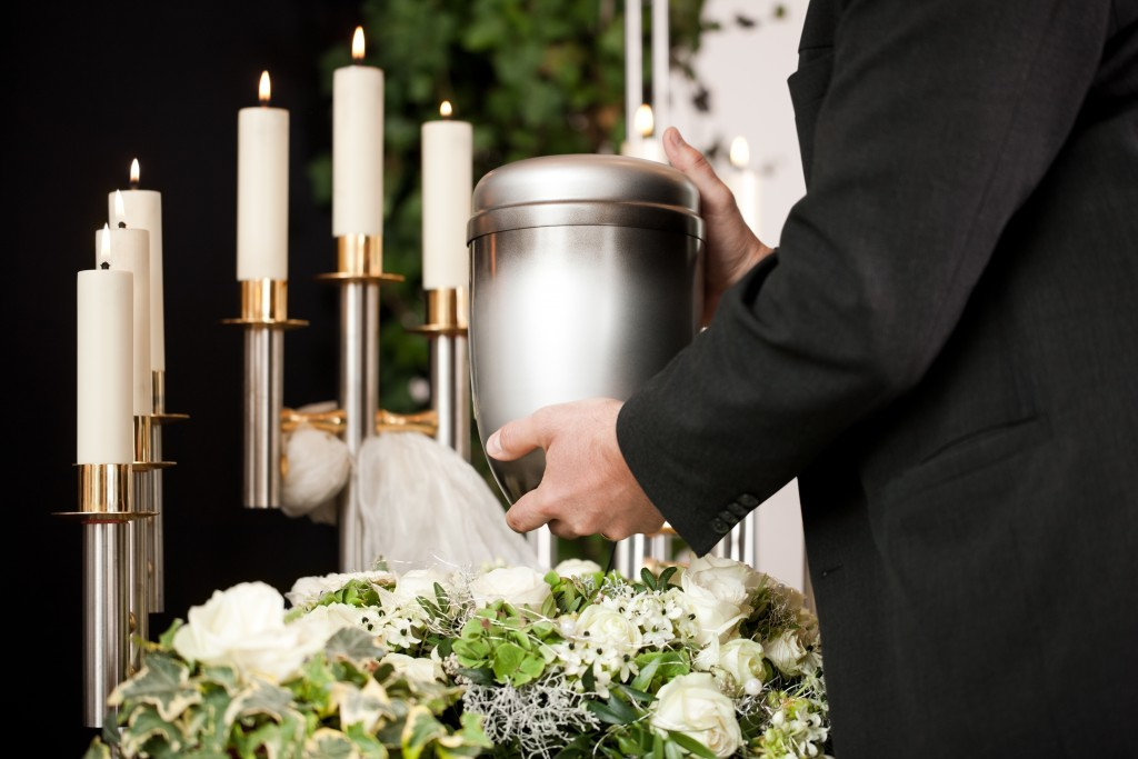 Funeral concept with urn, white roses, and candles
