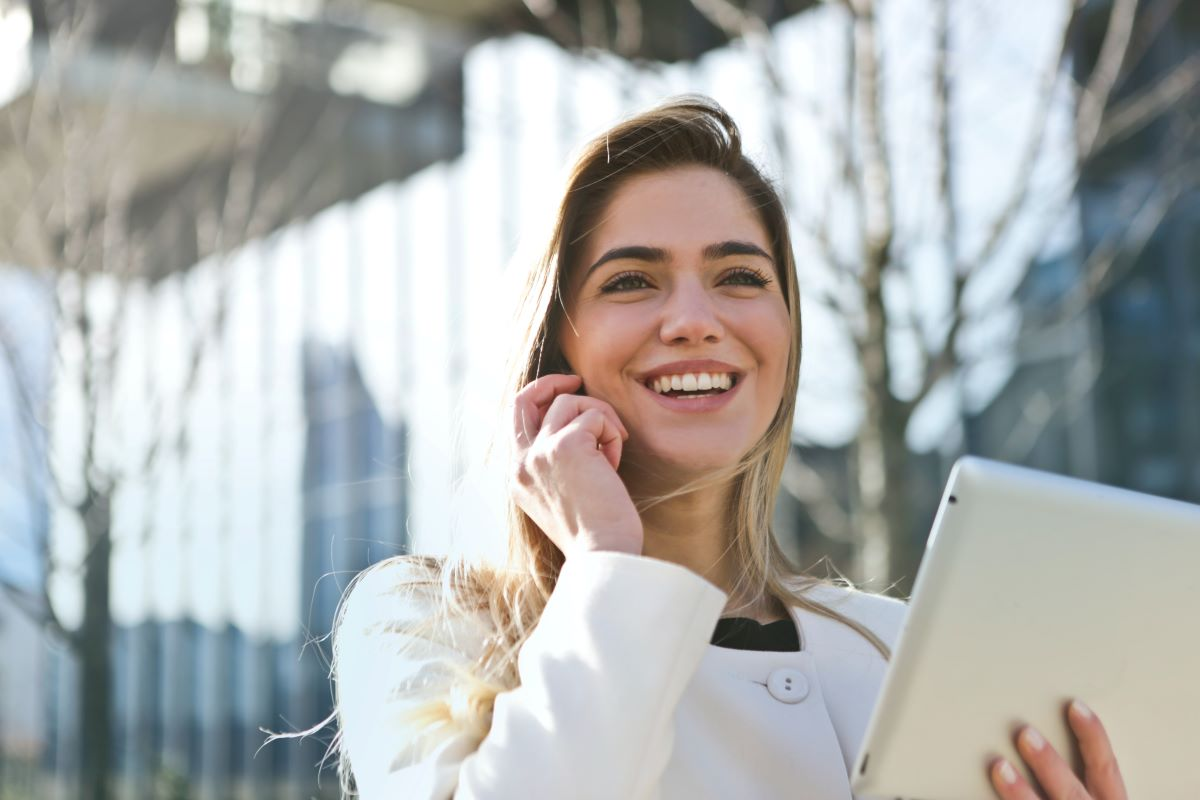 woman smiling while holding tablet