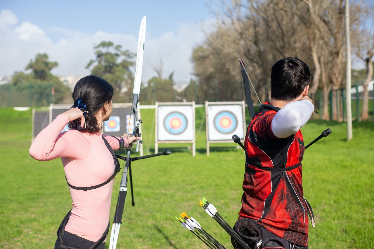 man and woman doing archery